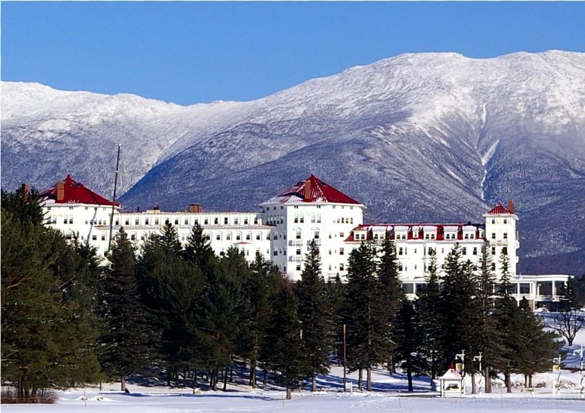 Zimowe wakacje, ferie zimowe w białych górach. Piękny, ogromny hotel wkomponowujący się w górski krajobraz.