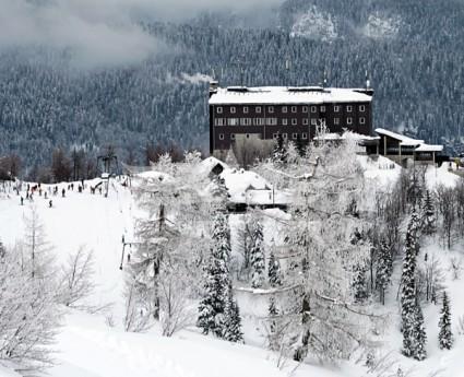 Śnieg okrywający górski krajobraz. W centrum ulokowany hotel, w którym kazdy ma możliwość zrelaksowania się i spędzenia niezapomnianych ferii zimowych.